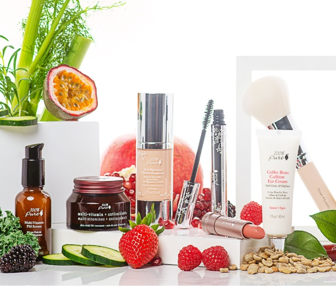 Clean beauty products from 100% Pure are lined up on white background next to fruit and nuts.