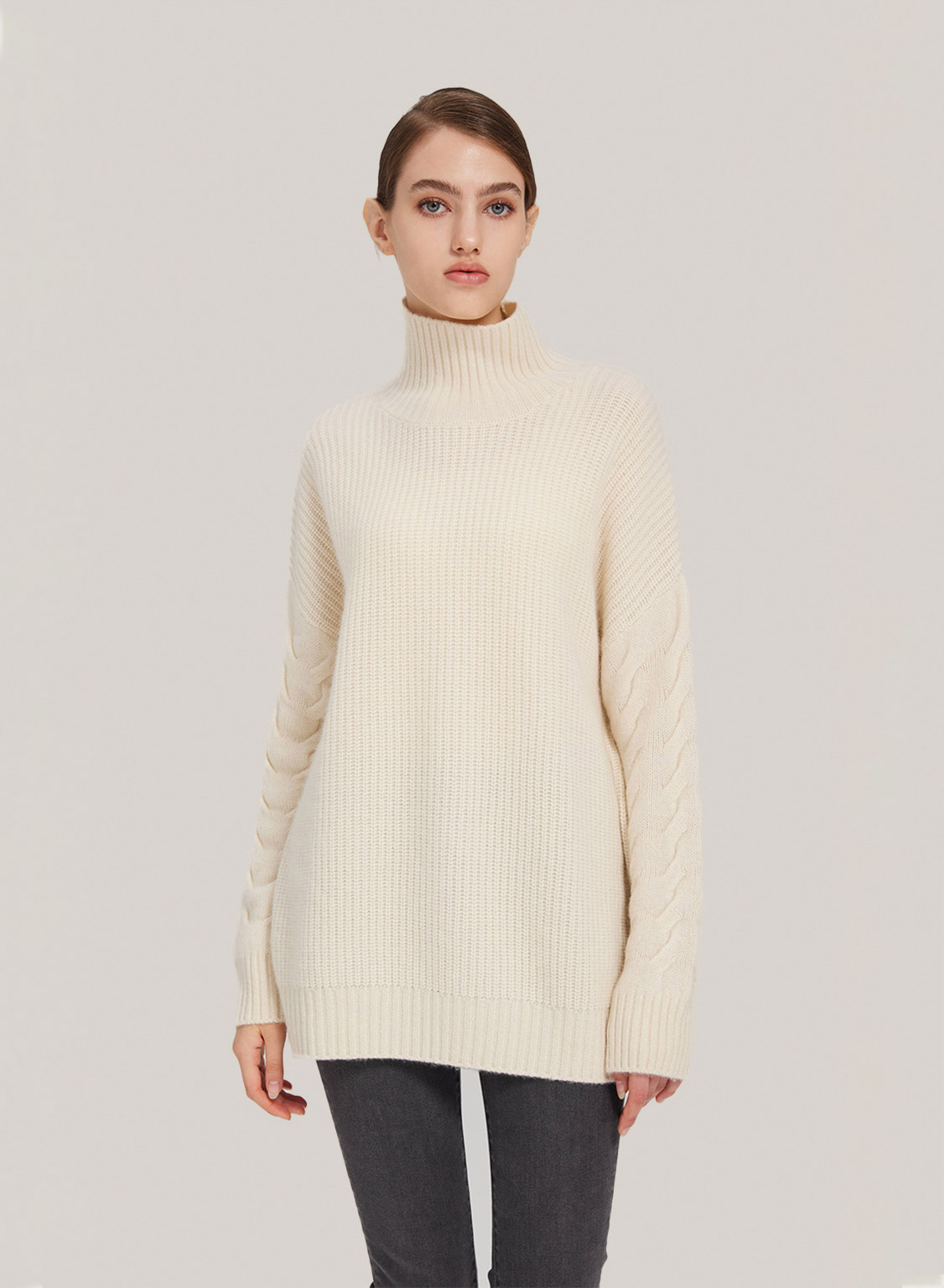 This sweater features a high neck, oversized fit, and cable-knit sleeve detailing. Definitely a must